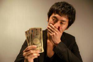 お金を見つめ悩む男性